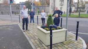 Members of Durrow Tidy Towns in front of planted container on The Square