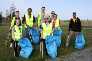 Eight people pose for photo with blue refuse sacks and litter pickers.